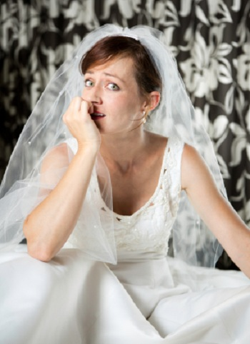 A young woman wearing a wedding dress and veil looks sideways and bites her nails nervously.