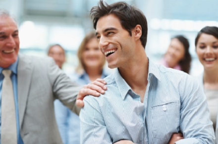 Portrait of smart young business executive enjoying success with team mates