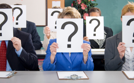 Group of business women and men sitting at table with question marks held in front of face