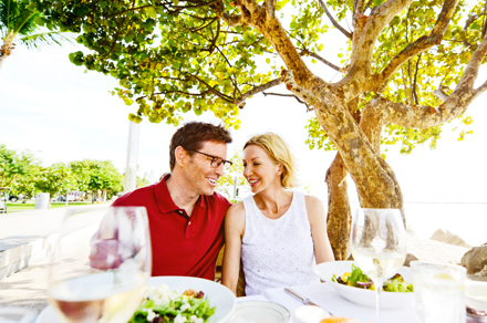 couple sitting together underneath a tree with a lunch table