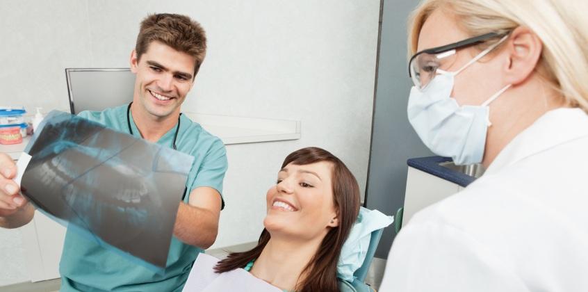patient, nurse, and dentist examining dental x rays