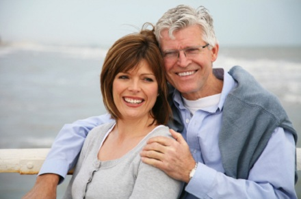 a man and a woman on a rocky beach smiling