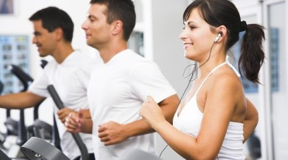 a man and a woman running on a treadmill in white shirts